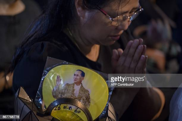 A woman bows down as she sees the royal vehicles pass by in a procession that took the relics of the late Thai king Bhumibol Adulyadej from the Grand...