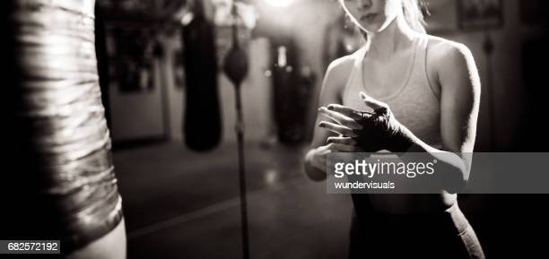 Woman boxer wrapping bandage around her hands for a fight