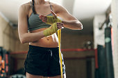 Woman boxer wrapping her hands in gym