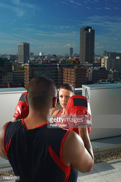 Woman boxing with coach on rooftop
