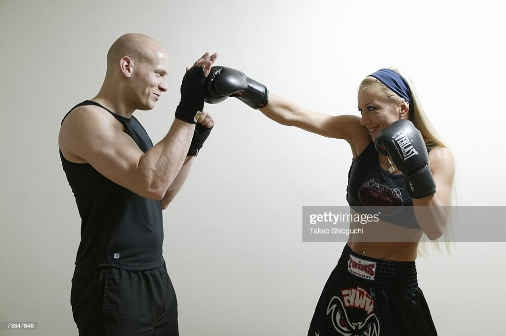 Woman boxing with trainer, studio shot : Stock Photo