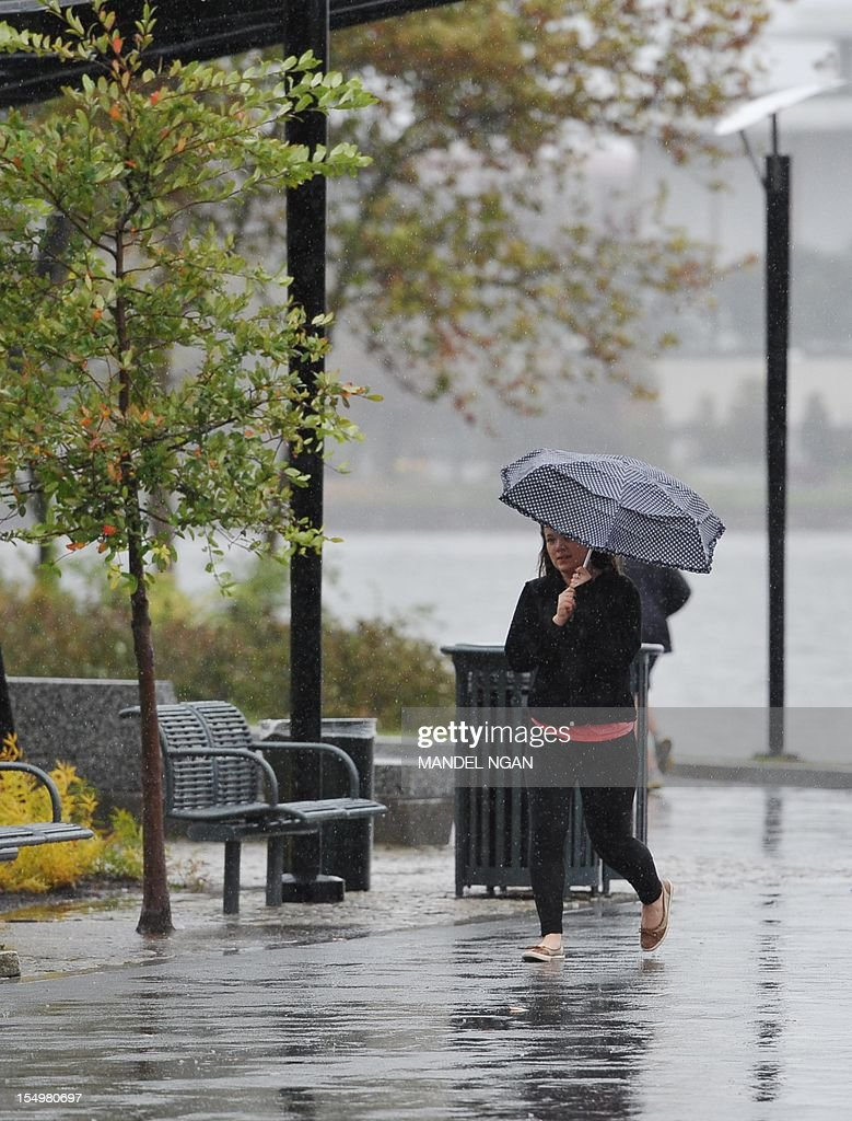 A woman braces her umbrella against a gust of wind while walking in the Georgetown Waterfront park along the Potomac River in the historic Georgetown neighbourhood of Washington on October 29, 2012 as Hurricane Sandy approaches. Sandy intensified as it roared toward the US East Coast, bringing New York, Washington and other major cities to a virtual standstill, amid warnings of life-threatening floods. AFP PHOTO/Mandel NGAN