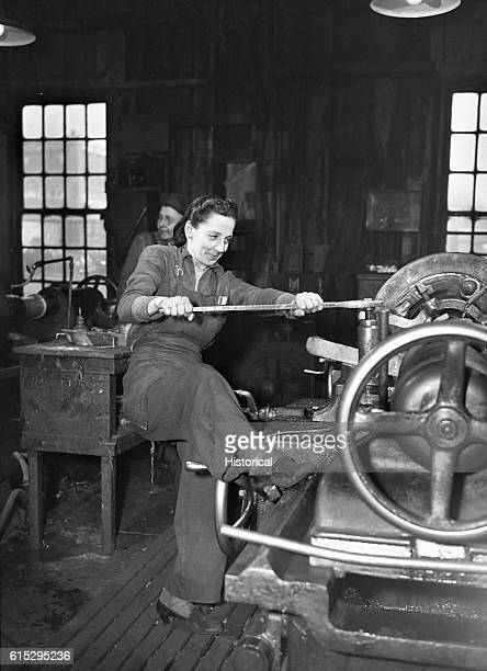 A woman braces with her foot to operate an axle lathe at a car wheel manufacturer in Buffalo New York The company began employing women for the war...