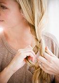 Woman braiding her hair, close up