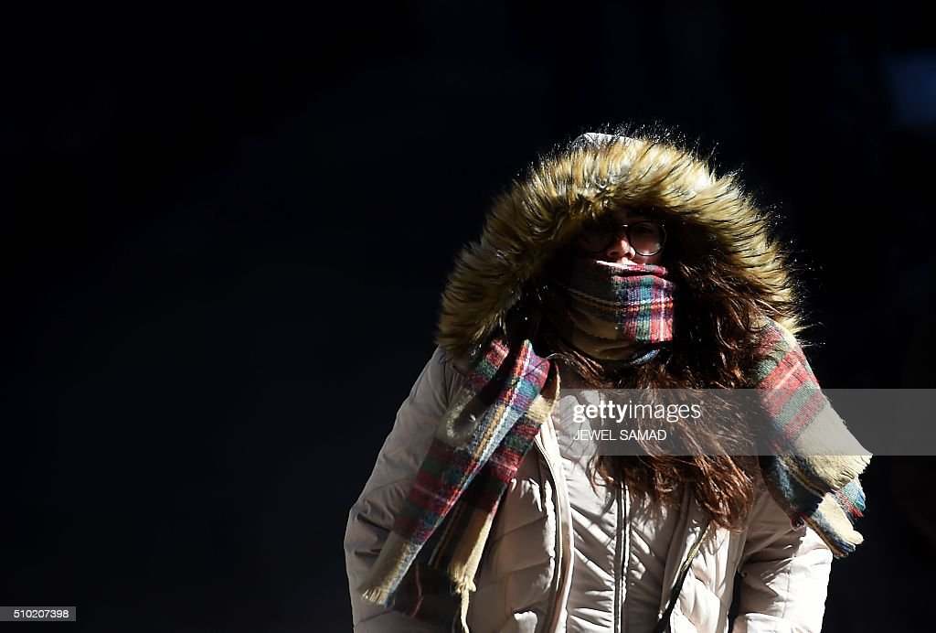 A woman braves the cold weather as she makes her way in downtown Manhattan, New York, on February 14, 2016. / AFP / Jewel Samad