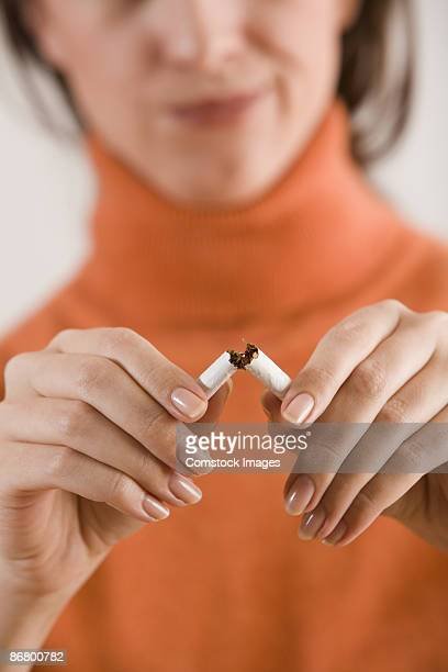 Woman breaking cigarette