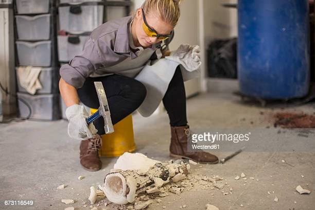Woman breaking off casts with hammer
