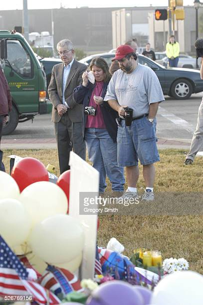 A woman breaks into tears just outside the gates of the Johnson Space Center where people came to leave flowers notes balloons and flags at a...