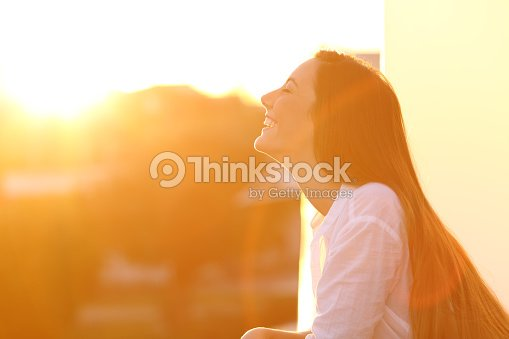 Woman breathing at sunset in a balcony : Stock Photo
