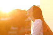 Side view portrait of a happy woman breathing deep fresh air at sunset in a house balcony