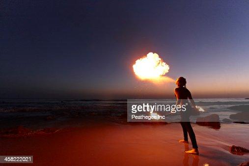Woman breathing fire on beach