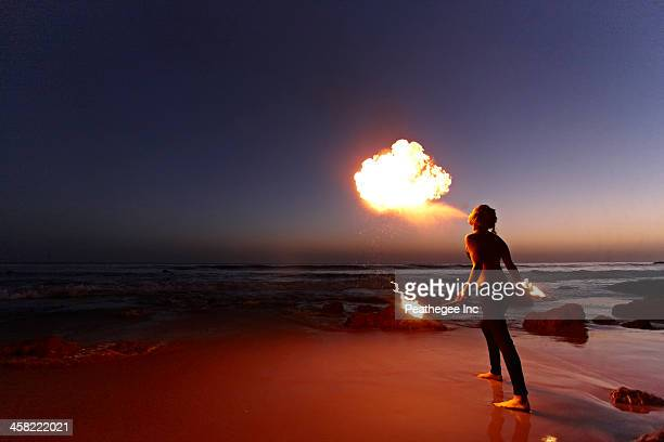 Woman breathing fire on beach