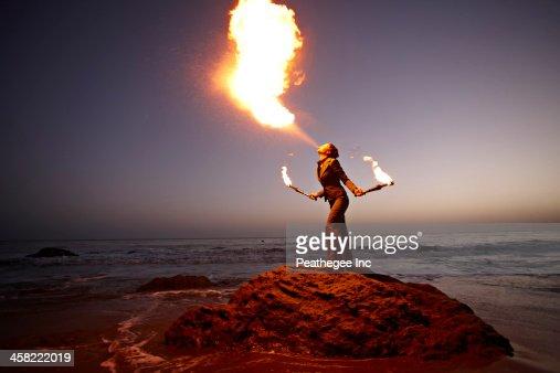 Woman breathing fire on rocky beach