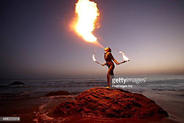 Woman breathing fire on rocky beach