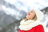 Happy woman breathing deep fresh air in winter on holidays in a snowy mountain