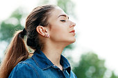 Young attractive woman breathing fresh air outdoors showing his face to the wind