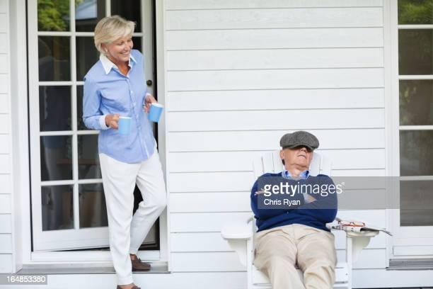 Woman bringing coffee to sleeping husband