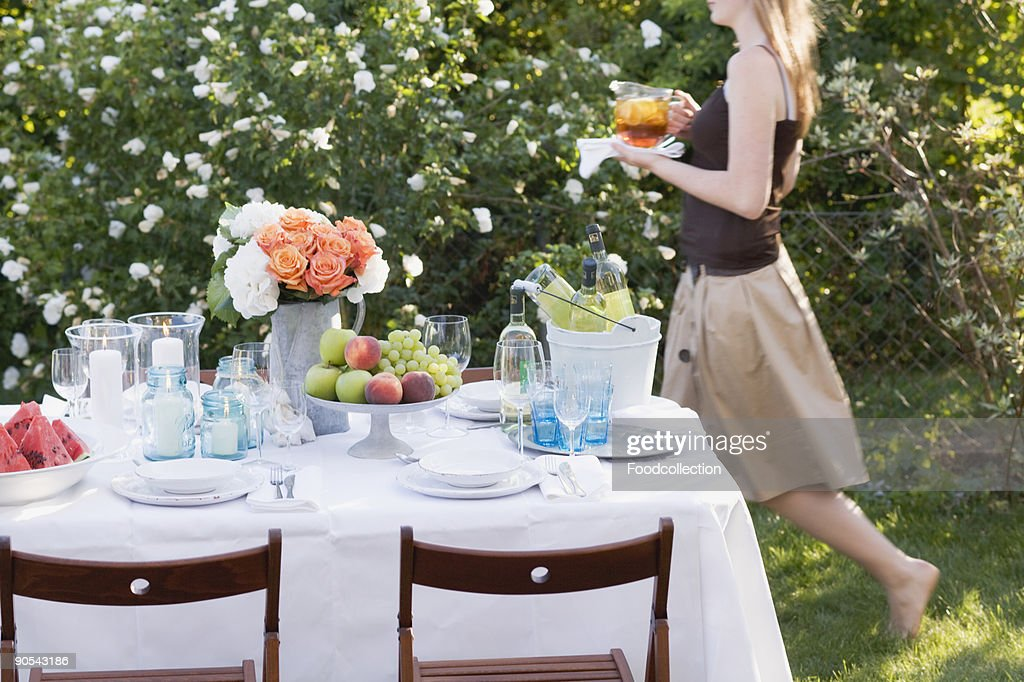 Woman bringing iced tea to table laid in garden, side view