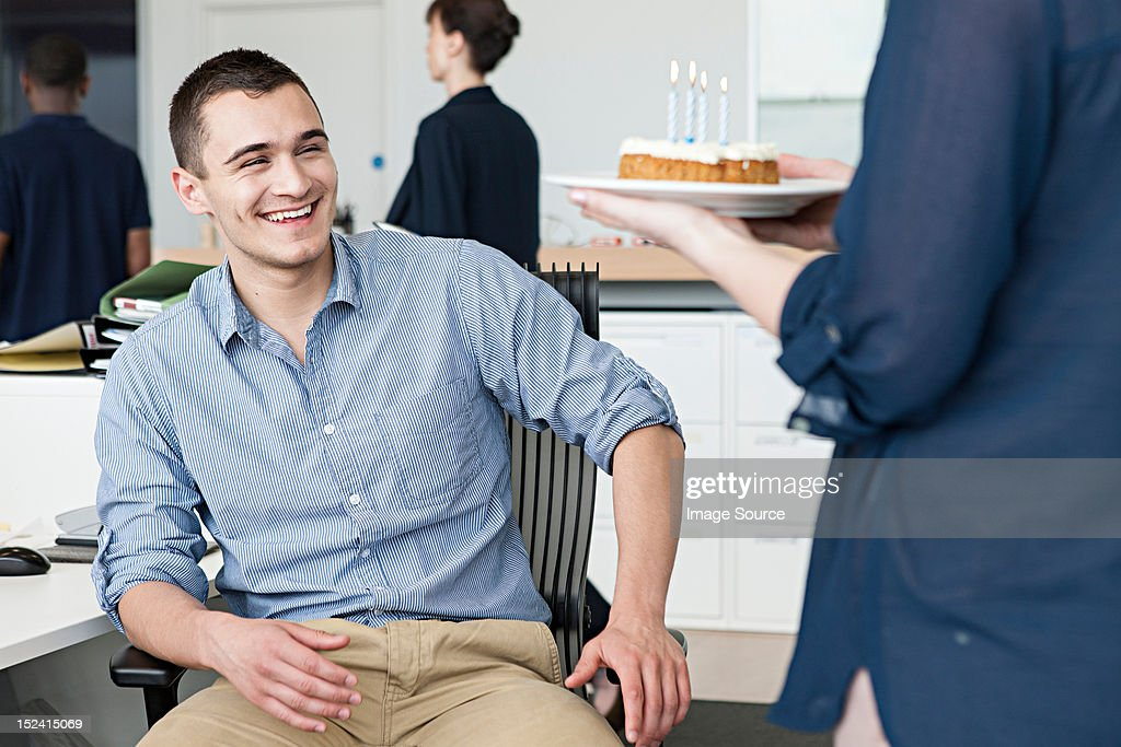 Woman bringing male colleague birthday cake in office : Stock Photo