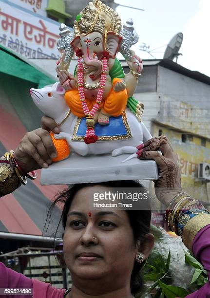 A woman bringing the idol of Lord Ganesh with dhol on the occasion of Ganesh Chaturthi on September 5 2016 in Indore India