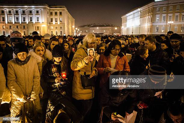 A woman brings a photo of one of the victims of the crash as people mourn the victims of Airbus A321 crash at the Palace Square on November 1 2015 in...