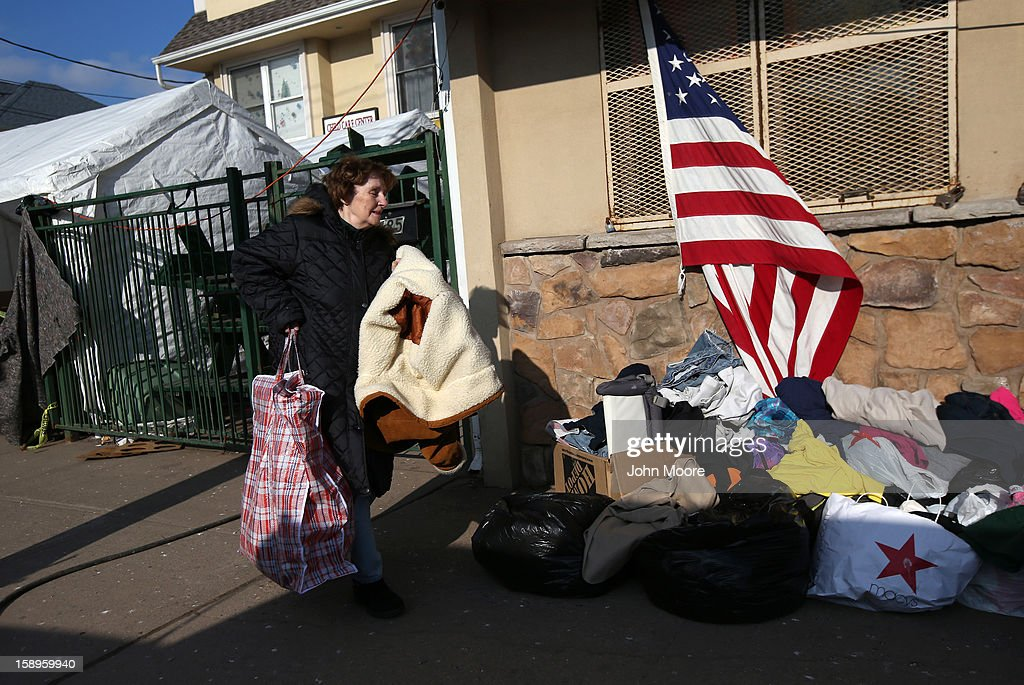 A woman brings clothing to donate at a Superstorm Sandy aid distribution center on January 4, 2013 in the Midland Beach area of the Staten Island borough of New York City. More than two months after the storm, Congress passed legislation today that will provide $9.7 billion to cover insurance claims filed by people whose homes were damaged or destroyed by Sandy.