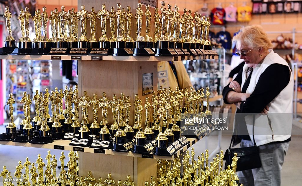 A woman browses a selection of mini statuettes like those presented to winners of the Academy Award on display and for sale at a retail shop catering primarily to tourists on the corner of Hollywood and Highland Avenues in Hollywood, California, on February 15, 2013. The 85th Academy Awards will take place in Hollywood on Sunday, Februaty 24. AFP PHOTO / Frederic J. BROWN