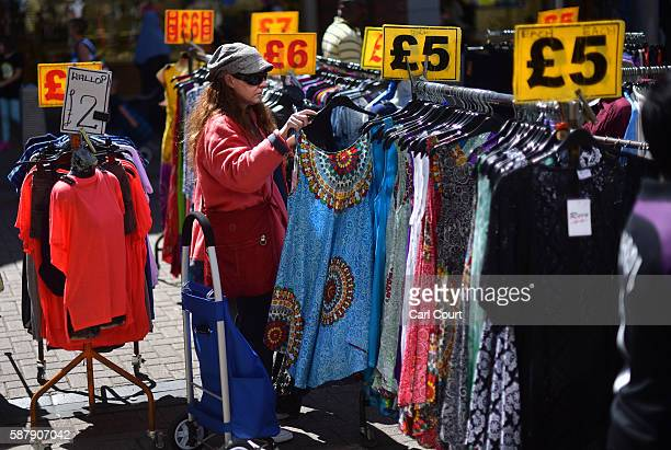 A woman browses dresses on sale at a stall in Walthamstow market on August 9 2016 in London England Walthamstow Market in north east London is...
