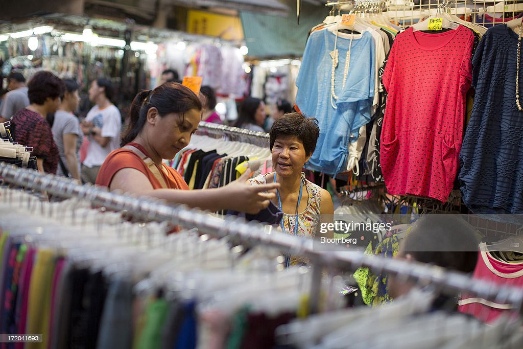 A woman browses for clothes in a market in the Mong Kok district of Hong Kong, China, on Sunday, June 30, 2013. Hong Kongs best-selling newspapers called on readers to join a march to mark the anniversary of the citys handover to China, saying the government has failed to address issues of poverty and universal suffrage. Photographer: Jerome Favre/Bloomberg via Getty Images