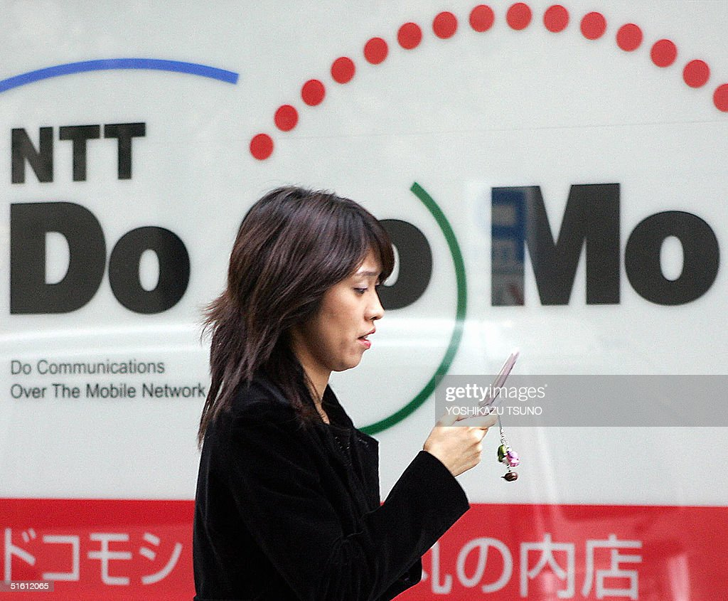 A woman browses her mobile phone as she walks past a NTT DoCoMo shop in Tokyo 29 October 2004 Japan's top mobile phone operator NTT DoCoMo said its...