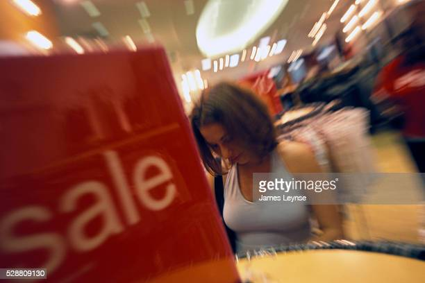A woman browses through a clothes rack during a 'back to school sale' at Wet Seal in the Garden State Plaza Mall in Paramus New Jersey