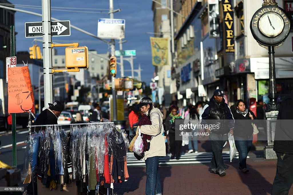 A woman browses through clothing at a roadside stall near Jamaica Avenue and 162nd street in Queens on October 24 one day after a hatchet attack on...