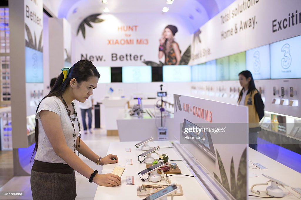A woman browses Xiaomi Corp. Mi3 and Redmi smartphones inside a 3 Hong Kong store, operated by Hutchison Whampoa Ltd., in Hong Kong, China, on Wednesday, April 30, 2014. Xiaomi, which sells more phones in China than Apple, is expanding to 10 more countries, including India and Brazil, after starting sales in Singapore earlier this year. Photographer: Brent Lewin/Bloomberg via Getty Images