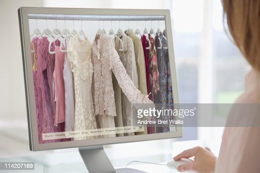 Woman browsing a digital clothes rail on-line : Stock Photo