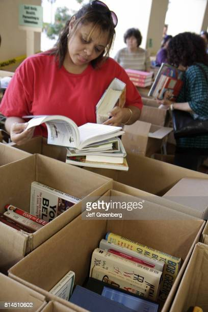 A woman browsing books at the MiamiDade Public Library Book Sale