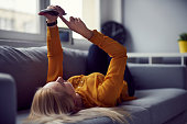 Woman browsing internet on her smartphone lying on the sofa at home