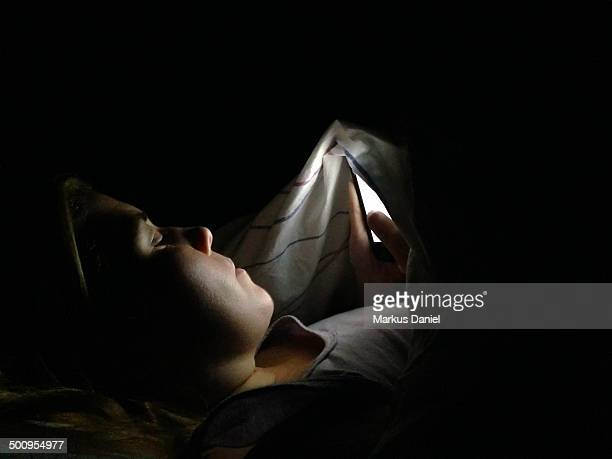 A woman browsing the internet and using her smartphone in the middle of the night under the covers to not disturb her husband
