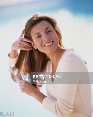 Woman brushing hair, blue sky in background, portrait : Stock Photo