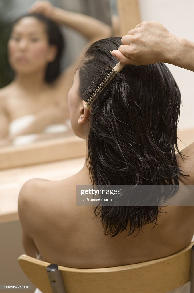 Woman brushing hair by mirror, rear view