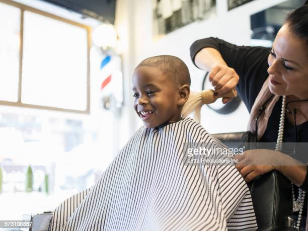 Woman brushing hairs from neck of boy in retro barbershop