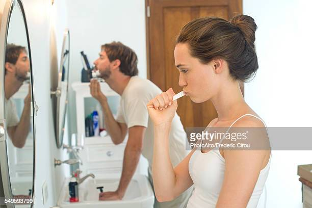 Woman brushing teeth, husband shaving