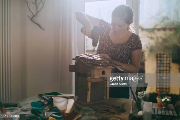 Woman building a bird house.