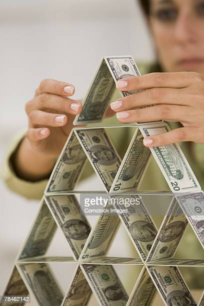 Woman building house of cards out of American money
