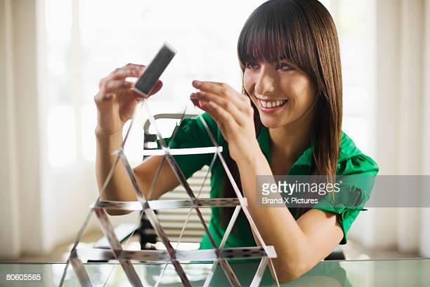 Woman building house of cards