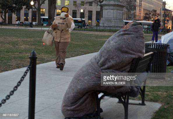 A woman bundled against the cold walks past a homeless man in McPherson Square as temperatures dipped into the single digits Fahrenheit and minus...