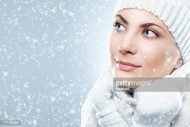 Woman bundled in white clothing as it snows