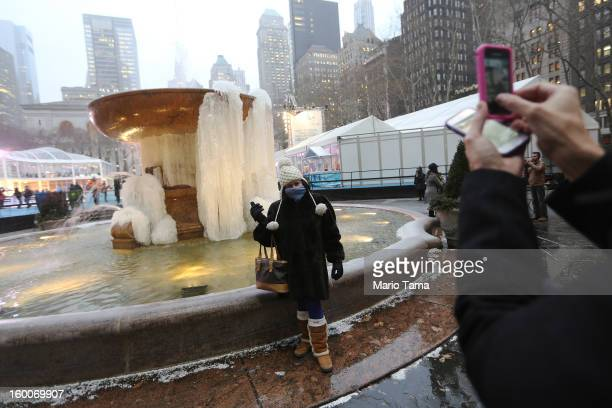 A woman bundled up against the cold poses next to the frozen fountain in Bryant Park in Manhattan on January 25 2013 in New York City Polar air...