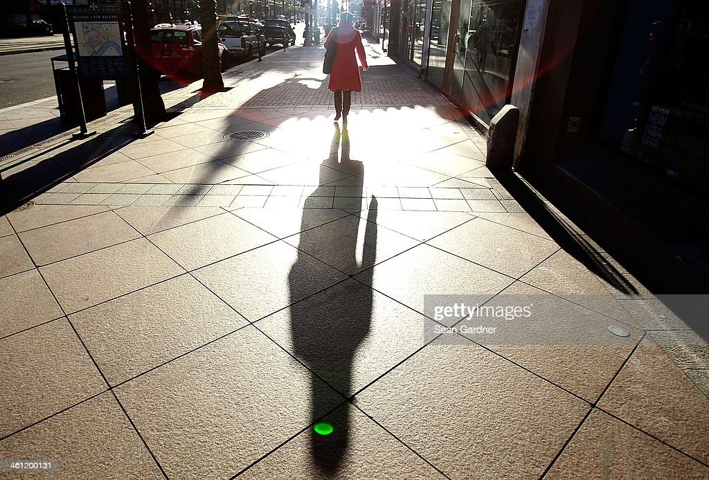 A woman bundled up in her coat walks to work along Canal Street as temperatures in the area plummeted below freezing on January 7 2014 in New Orleans...