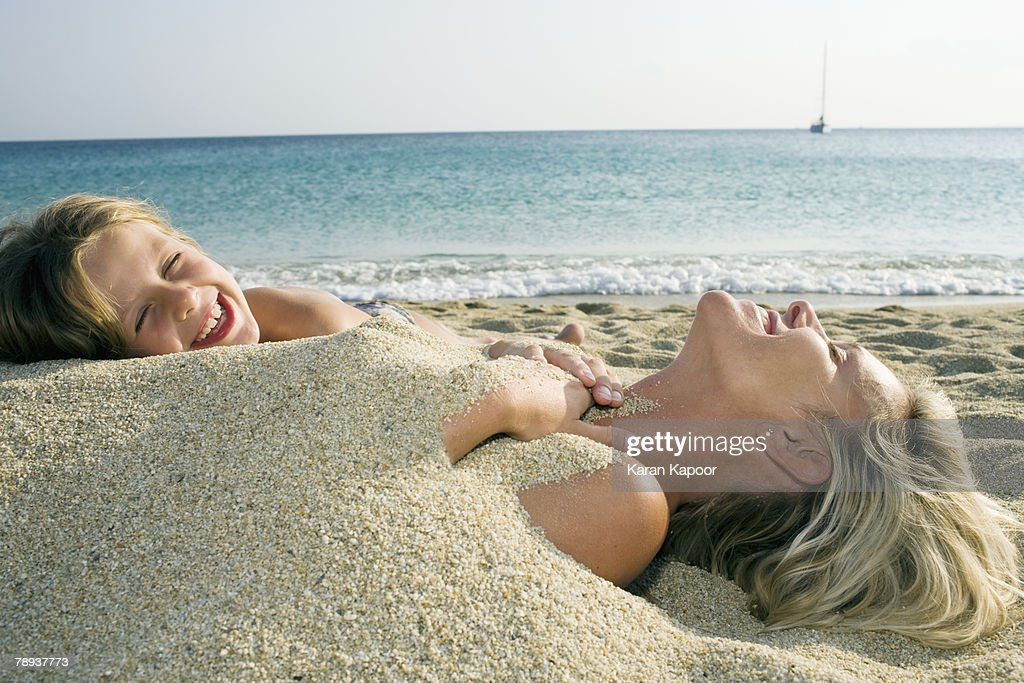 Woman buried in sand at the beach with young girl leaning on her and laughing.