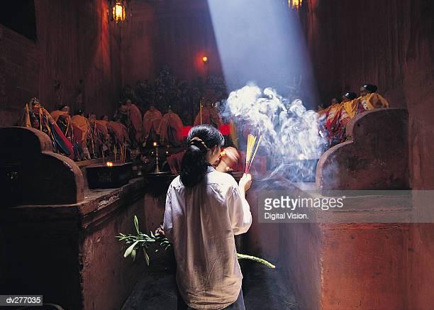 Woman burning incense, Vietnam